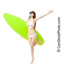 happy young woman running and holding surfboard