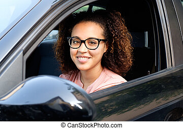 Happy young woman seated in her new car