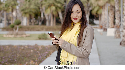 Happy young woman sending a text message - Happy attractive...