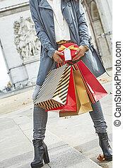 happy young woman shopper near Arc de Triomphe in Paris, France