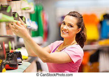 happy young woman shopping for sports footwear
