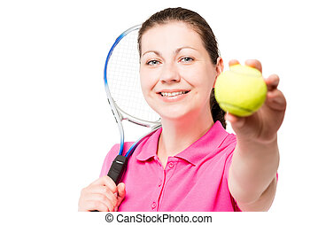 happy young woman showing a tennis ball on a white background