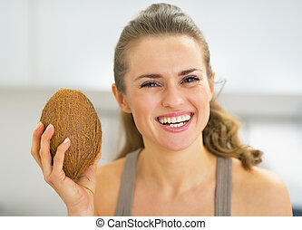 Happy young woman showing coconut