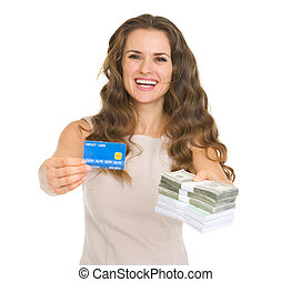 Happy young woman showing credit card and money packs