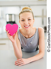 Happy young woman showing decorative heart in kitchen