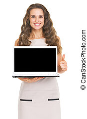 Happy young woman showing laptop blank screen showing thumbs up