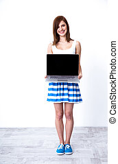 Happy young woman showing laptop blank screen