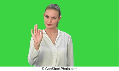 Happy young woman showing OK sign on a Green Screen, Chroma Key.
