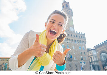 Happy young woman showing thumbs up in front of palazzo...