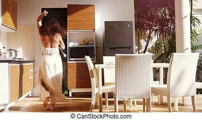 Happy young woman singing and dancing while cooking in the...
