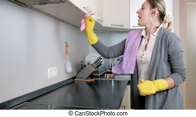Happy young woman singing and dancing while doing housework on kitchen