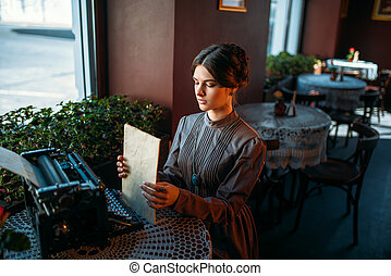 Happy young woman sits by the table in cafe