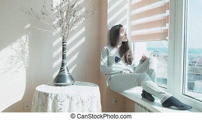 Happy young woman sits in the morning in the sun on a windowsill. A beautiful girl sits by the window in the sunshine from the curtains. A girl in pajamas, a vase with decorative flowers.