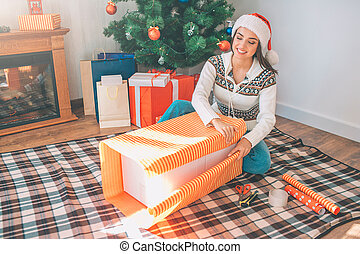 Happy young woman sits on floor and packs big box with orange-colored paper. She does it with pleasure. Brunette smiles. There are Christmas tree with prepared gifts behind her.