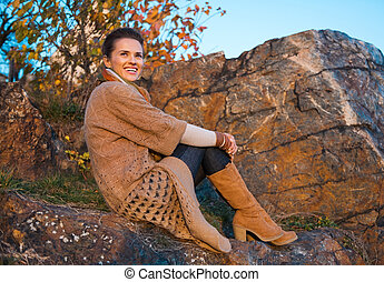 Happy young woman sitting in autumn outdoors in evening