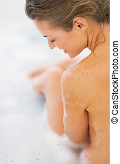 Happy young woman sitting in bathtub. rear view