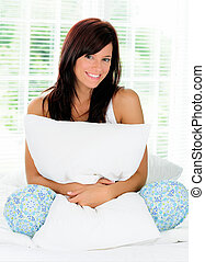 Happy Young Woman Sitting In Bed Hugging A Pillow