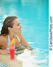 Happy young woman sitting in pool with cocktail