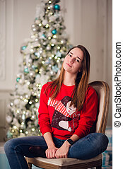 Happy young woman sitting near christmas tree.