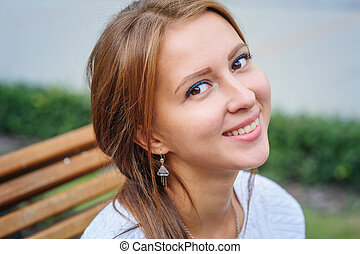 happy young woman sitting on a bench in the Park