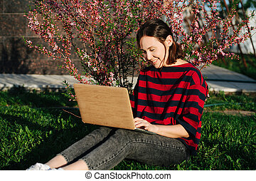 Happy young woman sitting on a lawn with laptop next to blossoming bush