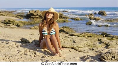 Happy young woman sitting on beach sand