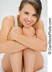 Happy young woman sitting on bed
