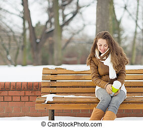 Happy young woman sitting on bench with hot beverage in...