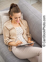 Happy young woman sitting on divan and using tablet pc