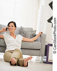 Happy young woman sitting on floor in living room and speaking mobile