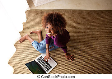 Happy young woman sitting on floor with laptop