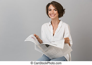 Happy young woman sitting on stool isolated over grey background holding newspaper reading.