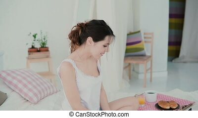 Happy young woman sitting on the bed and dancing. Brunette girl uses laptop, browses the Internet during breakfast.