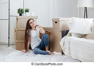 happy young woman sitting on the floor in her new apartment