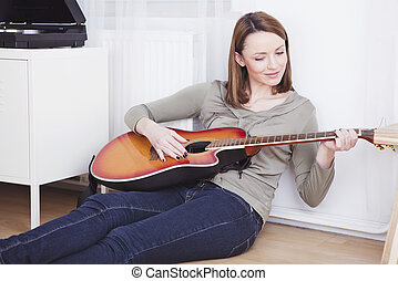 Happy young woman sitting on the floor playing guitar