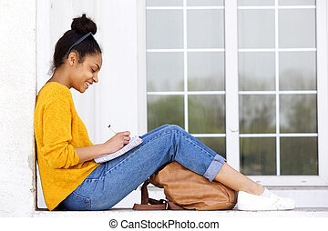 Happy young woman sitting outdoors writing a book