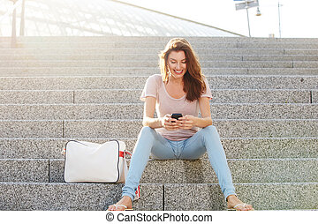 happy young woman sitting outside and looking at mobile phone
