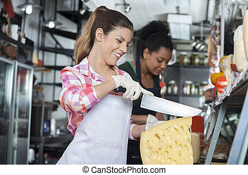 Happy Young Woman Slicing Cheese With Knife In Shop