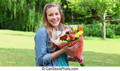 Happy young woman smelling flowers in the countryside