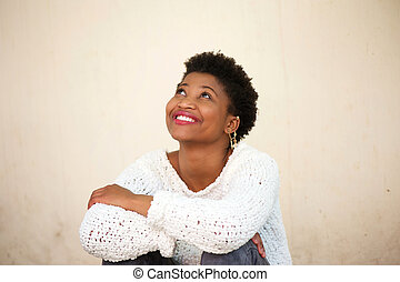 Happy young woman smiling and looking up