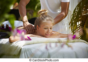 Young beautiful blonde caucasian woman gets massage and beauty treatment in luxury resort. Horizontal shape, side view