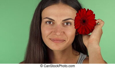 Happy young woman smiling, putting flower in her hair -...