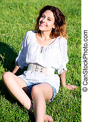Happy young woman smiling sitting in grass
