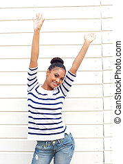 Happy young woman smiling with arms raised