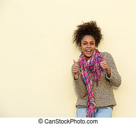 Happy young woman smiling with thumbs up sign