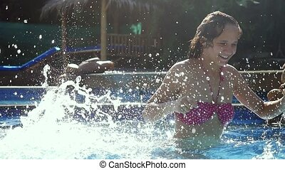 Happy young woman splashing in the pool in slow motion.
