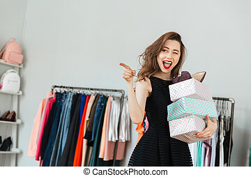 Happy young woman standing in clothes shop