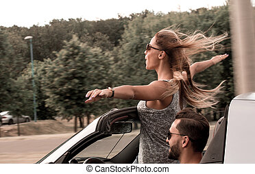 happy young woman standing in convertible car