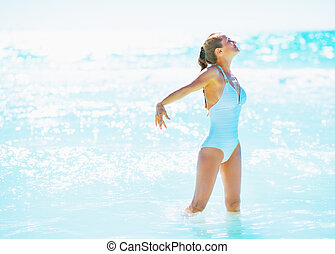 Happy young woman standing in sea and rejoicing