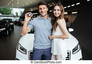 Happy young woman standing near car with boyfriend - Picture...